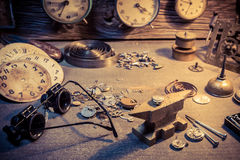 Old watchmaker's workshop with parts of clocks. Closeup of old watchmaker's workshop with parts of clocks Royalty Free Stock Photography