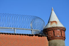 Old watchtower with barbwire on a prison wall Stock Photo