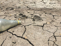 A old water bottle on dry and cracked ground make global warming Royalty Free Stock Images