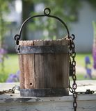 Old water bucket sitting on water well in Williamsburg Virginia stock images