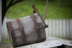 Old water bucket sitting on water well in Williamsburg Virginia stock photo
