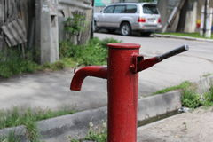 Old water hand pump in the center of the modern city. Stock Photos