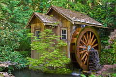 Old water mill. Rustic wooden water mill with wheel turning Royalty Free Stock Images