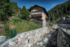 Old water mill for grain. Image of an old water mill made for grain production. The beautiful and historic building is located in the Italian Alps. The water Royalty Free Stock Image