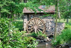 Old water mill with wheel. Stone mill with old water wheel in countryside next to river Royalty Free Stock Photo