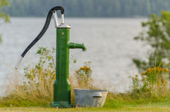 Old water pump. In front of a lake in summertime stock photos