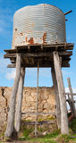 Old water tank. Disused rusty water tank elevated on a rotting wood structure Royalty Free Stock Photos