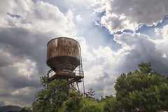 Old water tank shined by sun rays Stock Photography