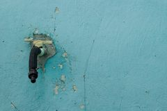 Old water tap on the background of an old blue wall with cracks stock photo
