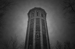 The old water tower. a frame from old movie. A frame from old movie. black and white. old tower and trees. mystic. horror. thick clouds Royalty Free Stock Photo