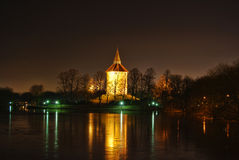 The old water tower at night. Winter night with bright reflections in the ice on the pond. The water tower is lit up with golden warm light and the trees in the stock photo