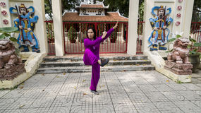 Tai Chi practice. Woman practice Thai Chi in front of old Buddhist temple Stock Image