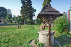 Old water well. With bucket and roof Royalty Free Stock Photography