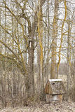 Old water well near the trees and birdhouse Royalty Free Stock Images