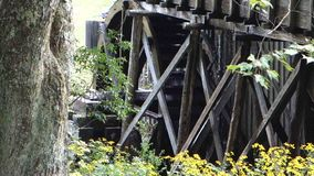 An old water wheel being turned at a preserved grist mill. An historic, working wheel generating power as seen at mabry mill, virginia stock footage
