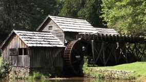 An old water wheel turning at a preserved grist mill stock video