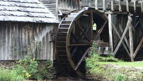An old water wheel turning at a preserved grist mill. Water powering a paddle-wheel at the historic mabry mill in virginia stock footage