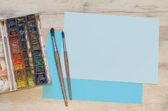 Old watercolor paintbox and blue pieces of paper Royalty Free Stock Photos