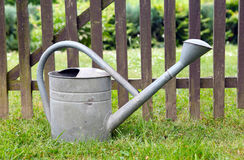 Old Watering can on the fence Royalty Free Stock Photography