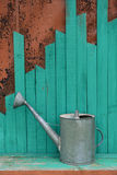 Old watering can on green planks Stock Photos