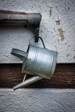 The old watering can and rocker on wall of  farmhouse Stock Photography