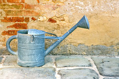 Old watering can by a rustic brickwall Royalty Free Stock Image