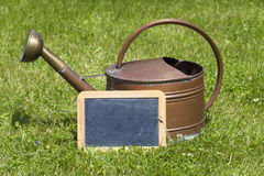 Old watering can and a slate Royalty Free Stock Photo