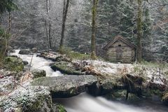 Old watermill in the forest. Old watermill by the river in the forest in Norway. The water runs under a small stone bridge in a winter forest landscape. Nature Royalty Free Stock Photo