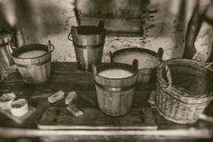Old way of making cheese and diary products, buckets of milk, cream and soured milk on wooden table royalty free stock photos