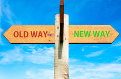 Old Way and New Way signs, Life change conceptual image. Wooden signpost with two opposite arrows over clear blue sky, Old Way and New Way signs, Life change Stock Image