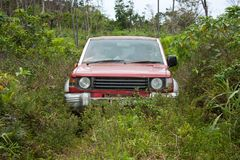 An old 4WD car going through the bush in Eua in Tonga. An old red 4WD car going through the bush in Eua in Tonga day gear hobby daylight challenge land rally royalty free stock images