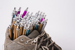 Old wear out sneaker is used like  pen holder Royalty Free Stock Photos