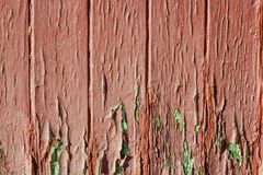 Fragment of old weather-beaten red door, surface with chapped textured paint Royalty Free Stock Image
