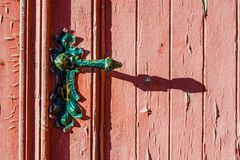 old weather-beaten red door with old vintage door knob, surface with chapped textured paint Royalty Free Stock Photo