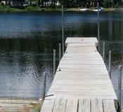 Old weatherbeaten dock. Wooden dock over dark blue rippled lake water.  Sebago Lake, Sebago, Maine, summer 2015 Stock Photography