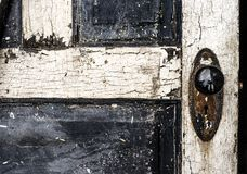 Old weathered antique beat-up wood panel door with chipped peeling paint and black porcelain doorknob and rusty plate. Old weathered antique beat-up wood panel Royalty Free Stock Image