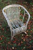 Broken old and weathered cane chair with armrests Stock Photography