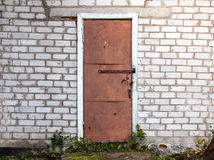 Old weathered barn door and brick wall. Stock Photography