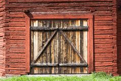 Old weathered barn door on a historic barn painted with the famous Falu  red paint Stock Image