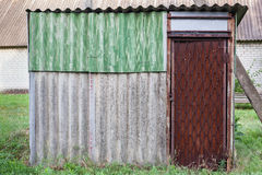 Old weathered barn with metal door. Royalty Free Stock Images
