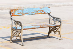 Old and weathered bench. Old and weathered wooden bench with cast aluminium legs on concrete floor in strong sunlight royalty free stock images