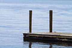 Old Weathered Boat Dock At The Lake. A single old, weathered, floating, boat dock made of wood planks and posts at the lake on an overcast day Royalty Free Stock Photos