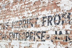 Old Weathered Brick Wall with Advertisement. Old Weathered Brick Wall with Decaying Advertisement Writing Stock Images