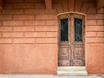 Old weathered brown door made of wood, orange wall in Croatia. Island Cres royalty free stock photography