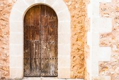 Old weathered brown wood front door with natural stone facade. Vintage brown wooden front door with rustic nature stone wall background stock image