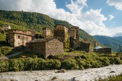 Old weathered buildings against small river stream against hills, Ushguli,. Svaneti, georgia royalty free stock photo