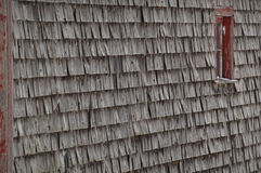 Old weathered cedar shakes shingles barn with red window Royalty Free Stock Photography