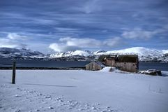 Old weathered and damaged barn on frosty snowy field with blue fjord and sky backdrop with mighty mountain peaks in the arctic cir Royalty Free Stock Images
