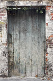 Old weathered deteriorated wooden door. In an old red brick wall with plaster spots Stock Images
