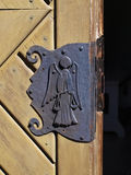 An old weathered door with a decoration on a lock. Of an angel holding a scale Royalty Free Stock Photos